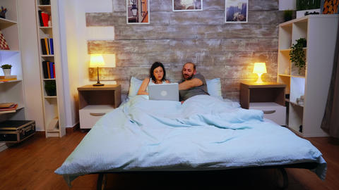 Zoom in shot of couple laying in bed under the blanket Live Action