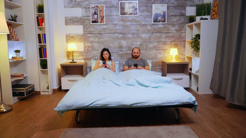 Zoom in shot of couple laying in comfortable bed Live Action