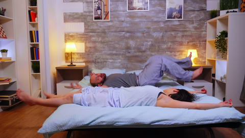 Young married couple falling back on bed after a crazy day at work Live Action