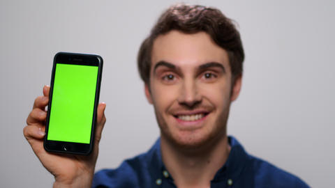 Man showing smartphone with green screen. Male showing phone with chroma key Live Action