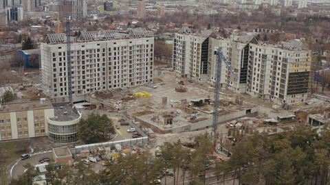 Top view of construction site, hoisting construction cranes and the construction Live Action