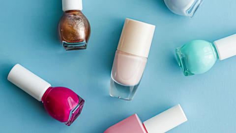 Bottles of nail polish on blue background, beauty cosmetics and make-up Live Action