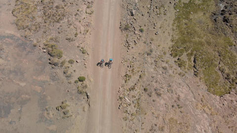 Aerial following two mountain bikers up a dry gravel road mountain pass Live Action