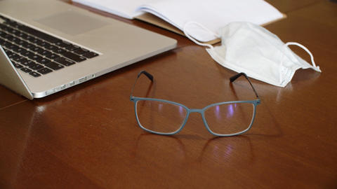 Glasses on wooden table on laptop, protective mask and daily planner background Live Action