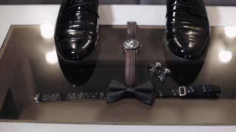 Wedding grooms bow tie, cufflinks, clock and shoes lie on glass table Live Action