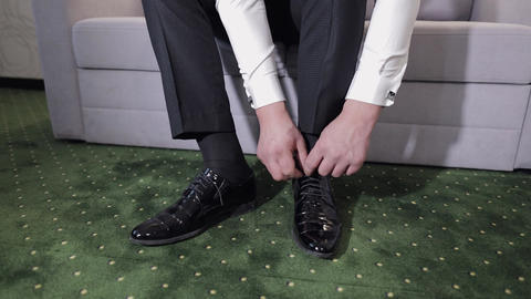 Groom putting his wedding shoes on wedding day. Hands of wedding groom Live Action