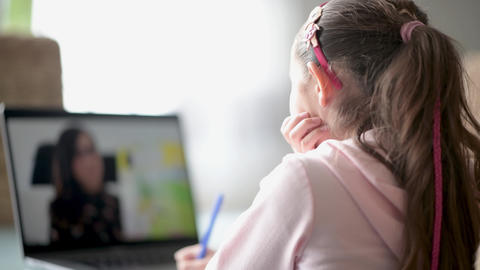 Young girl of primary school studying at home with her grandma, internet chat Live Action