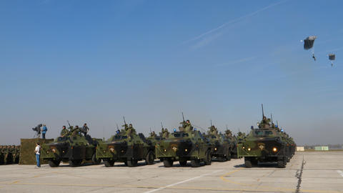 Armored Military Vehicles in Green Mimetic Camouflage with Paratroopers Flight Live Action