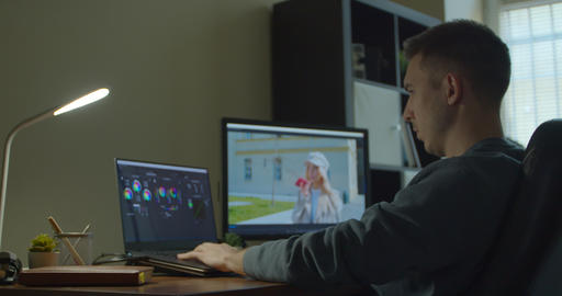 Man working on computer with Two Monitors Color Correction Post Production video Live Action