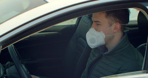 Man in car with surgical mask on face against Coronavirus Disease 2019. COVID-19 Live Action