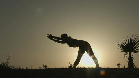 Female silhouette doing body stretching exercises, practicing yoga in sunlight Footage