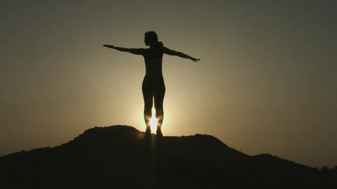 Young female doing stretching exercises early in the morning on mountain top Footage