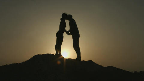 Silhouette of young couple in love hugging, kissing in sunset rays on mountain Footage