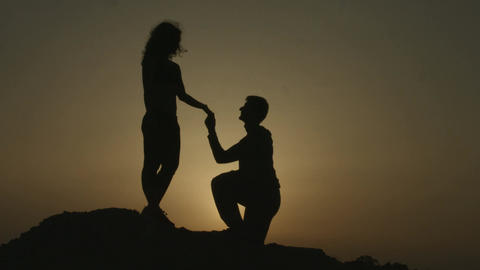 Silhouette of young man proposing to girlfriend on his knee, romantic engagement Footage