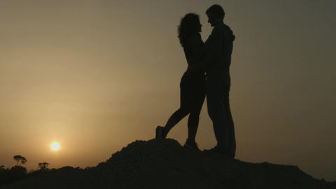 Romantic story of two people in love. Silhouette of couple kissing at sunset Footage
