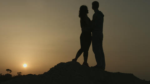 Happy girl kissing boyfriend. Couple hugging, enjoying view of amazing sunset Footage