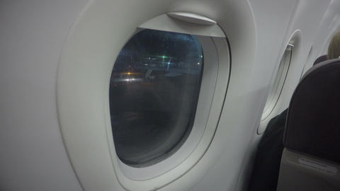 Airplane passenger looking through plane window at airport. Night flight delay Footage