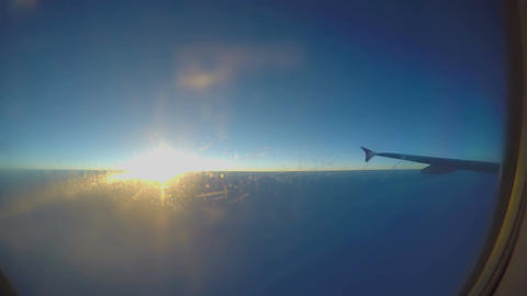 Beautiful sunrise in sky, plane wing seen through aircraft window, passenger pov Footage