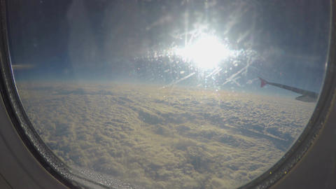 Water drops on glass of aircraft window. Passenger plane flying above clouds Footage