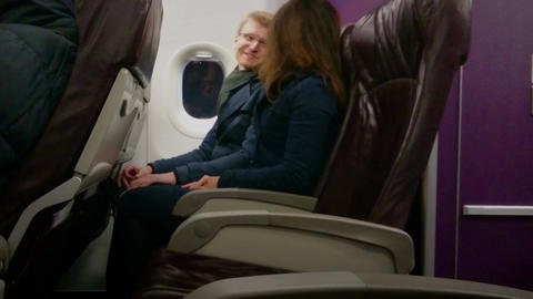 Happy couple traveling by plane on vacation, holding hands, enjoying flight Footage