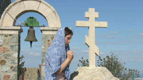Religious woman praying to God, crossing herself, looking into the sky with hope Footage