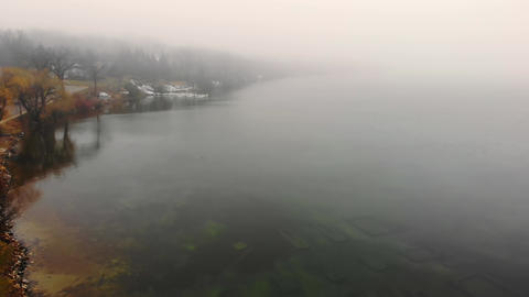 Aerial Flying over the lake in heavy fog and cloudy weather. The embankment of Live Action