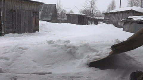 Snowfall in village and snow removal with wooden shovel Live Action