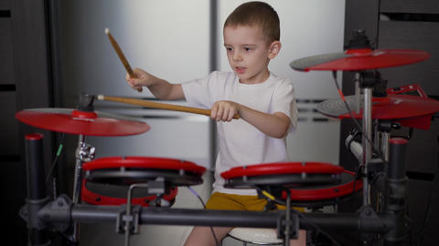 A boy plays electronic drums at home. A little boy enjoys playing the electronic Live Action