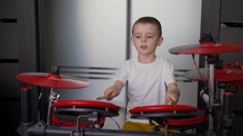A boy plays electronic drums at home. A little boy enjoys…, Live Action