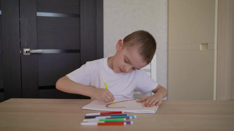 A little boy sits at a table and draws. A dark-haired little boy sits at a table Live Action