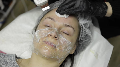 Cosmetologist make ultrasonic face cleaning on woman face in beauty clinic salon Live Action