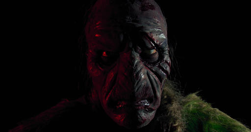 Ugly orc with the scary face is staring in the dark room, close up, 4k Live Action
