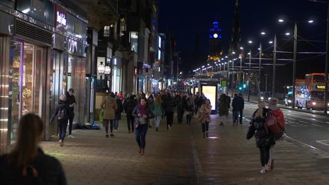 Pedestrians walking at Princes Street Edinburgh at night Live Action
