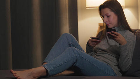Woman lying on the couch in a cozy room and makes an online purchase using a Live Action
