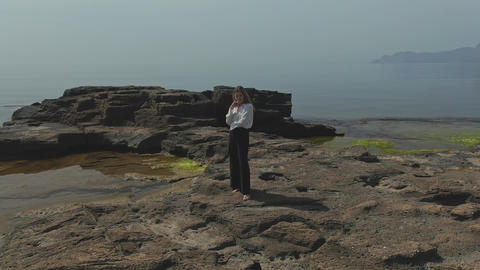 Aerial filming of a young woman with her feet stands on a rocky sea shore GIF