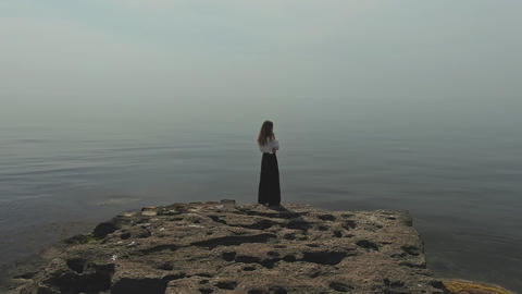 Aerial footage of a young woman standing on a stone by the sea hair flutters in GIF