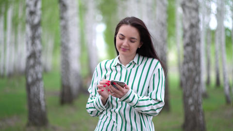 beautiful girl with a smartphone in her hands walks along a birch grove in Live Action