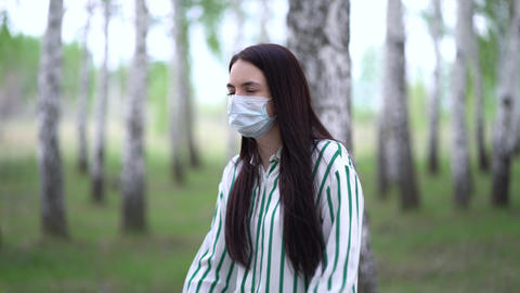 Stylish woman in a medical mask on a walk in the birch forest Live Action