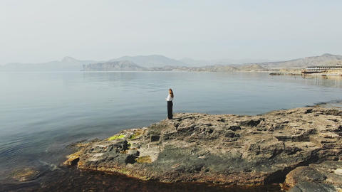 female figure against the backdrop of the sea bay surrounded by mountains with Live Action