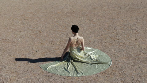 A young woman in an evening dress sits on a sand Art deco woman Ar nuvo fashon Live Action