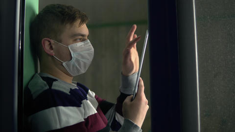 A young man is sitting at home in quarantine with a tablet in his hands. A man Live Action