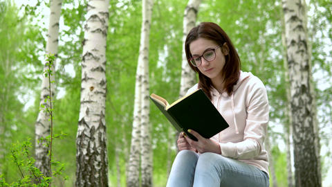 A young woman is sitting in nature with a book in her hands. A girl sits on a Live Action