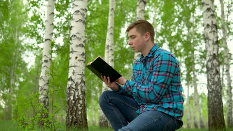 A young man is sitting in nature with a book in his hands. A man sits on a stump Live Action