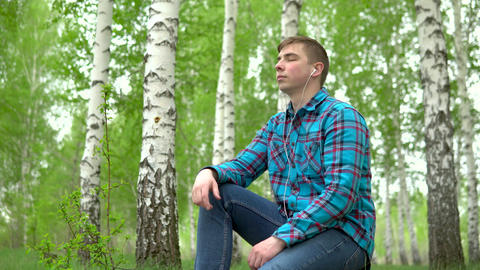 A young man sits in nature with headphones in his ears. A man sits on a stump in Live Action