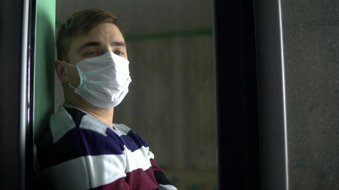 Sad young man is sitting at home in quarantine. A man sits on a window sill in a Live Action