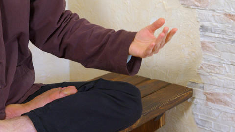 Male body in lotus pose while spiritual meditation. Male legs and hands in zen GIF