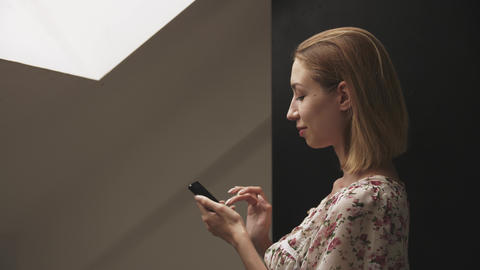 Young woman in profile works on smartphone GIF