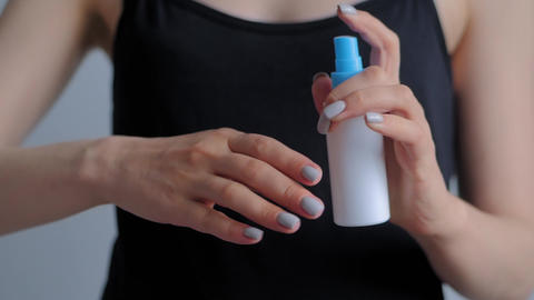 Slow motion: woman spraying antiseptic on hands - close up - spray disinfection Live Action