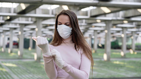 Woman in medical protective mask wears protective rubber gloves Live Action