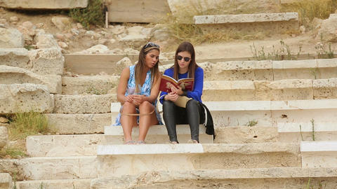 Two beautiful women reading tourist guide, planning sightseeing tour together Footage
